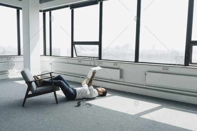 Mature businessman lying on the floor in empty office using laptop