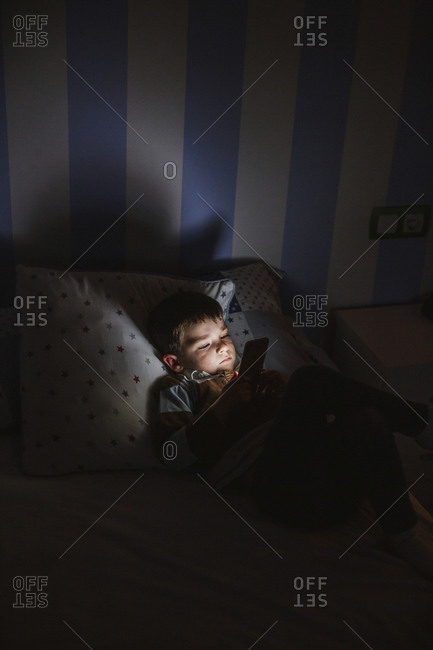 Little boy in bed using smartphone at night