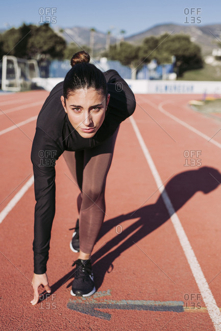 Young woman on tartan track starting