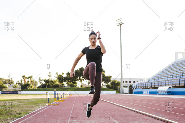 Young woman on tartan track running