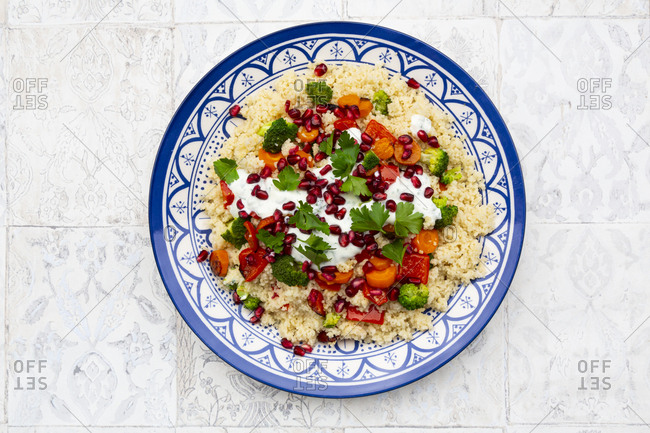 Couscous with grilled vegetables: carrots- peppers and broccoli and yoghurt-mint sauce- parsley- pomegranate seeds