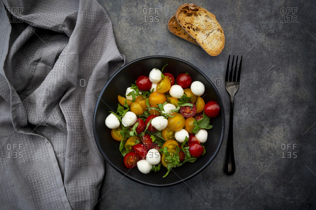 Overhead view of salad with arugula- mozzarella- cherry tomatoes and basil