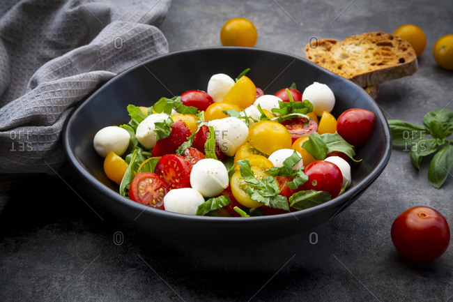 Bowl of salad with arugula- mozzarella- cherry tomatoes and basil