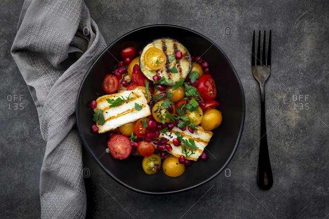 Bowl of Persian salad with tomatoes- grilled halloumi cheese- eggplant- pomegranate seeds- sumac- black sesame and parsley