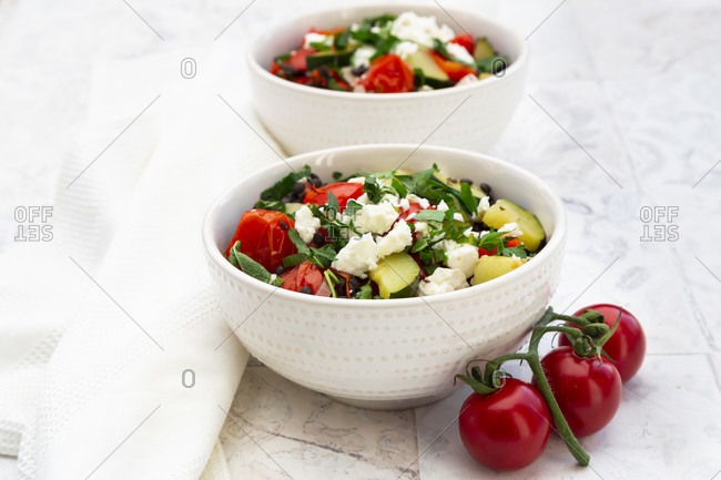 Bowls of salad with beluga lentils- tomatoes- paprika- zucchini- feta cheese- mint and parsley