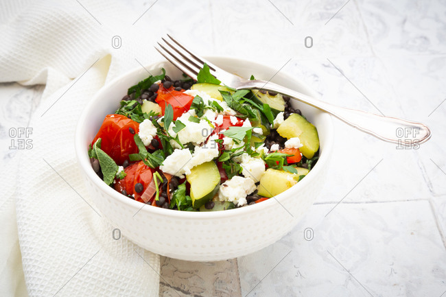 Bowl of salad with beluga lentils- tomatoes- paprika- zucchini- feta cheese- mint and parsley
