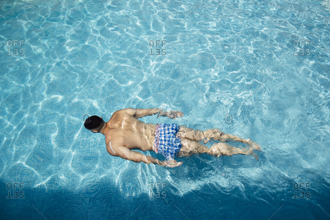 Back view of man floating in swimming pool