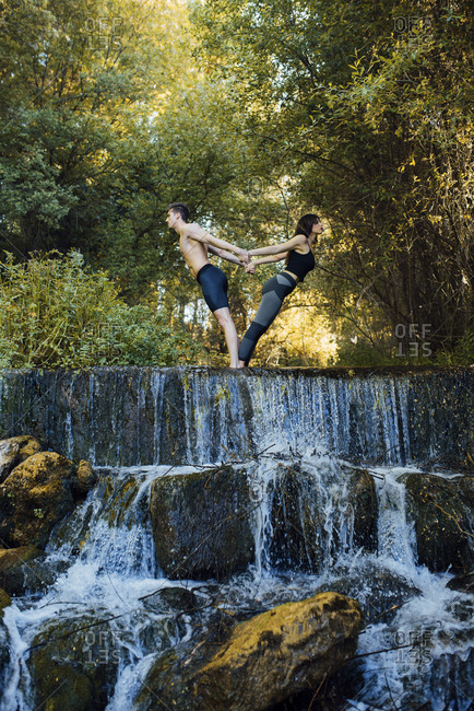 Couple practicing acro yoga together on a waterfall