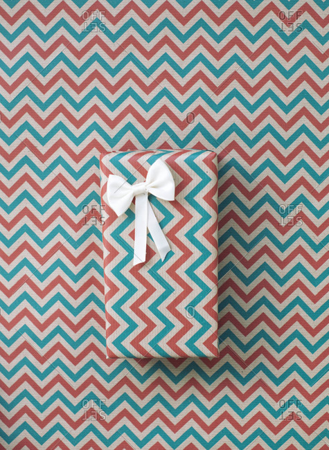 Christmas gift in a zig zag wrap on a same pattern background