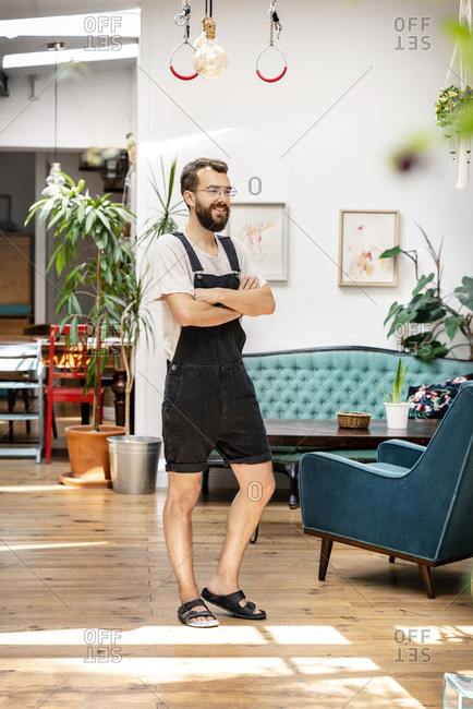 Young man in dungarees standing in his living room- with arms crossed