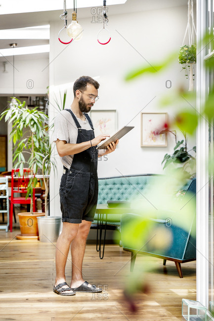Young man in dungarees standing in his living room- using digital tablet