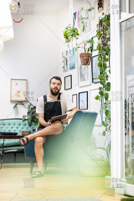 Young man in dungarees sitting in his living room- using digital tablet