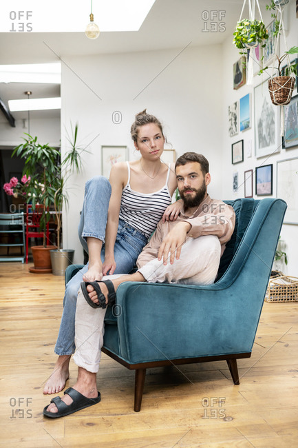Young couple sitting in arm chair- portrait