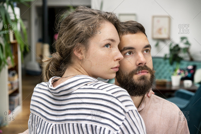 Young couple with arms around- looking insecure