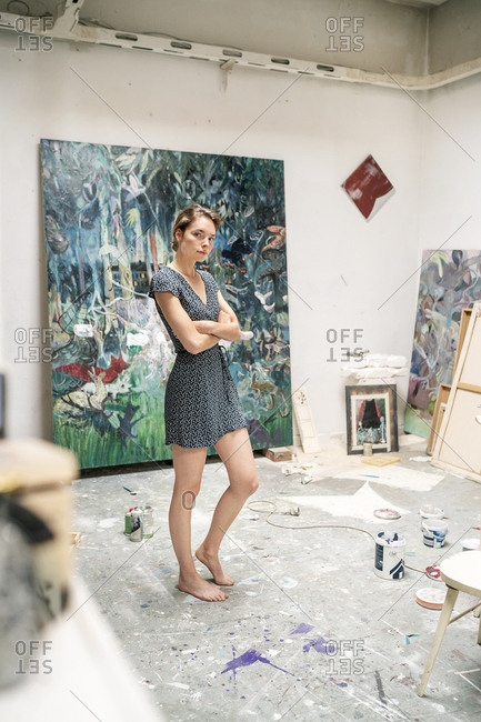 Young artist standing in her studio- with arms crossed