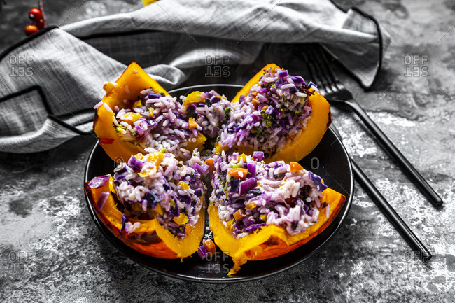 Quartered Hokkaido squash filled with rice- red cabbage- paprika- broccoli- onions and carrots