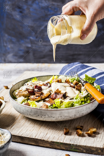 Hand of person pouring dressing over bowl of Caesar salad with romaine lettuce- Parmesan cheese- bacon- chicken breast and croutons