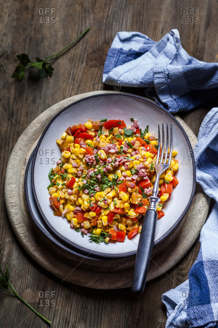 Bowl of warm corn salad with bell pepper- potatoes and diced ham
