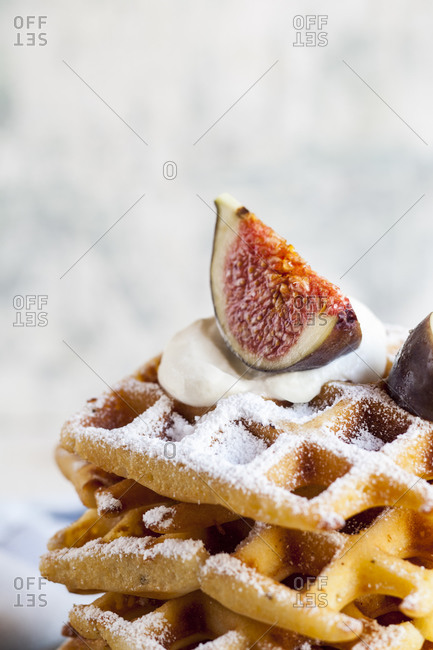 Stack of thick Belgian waffles with whipped cream- powdered sugar and figs