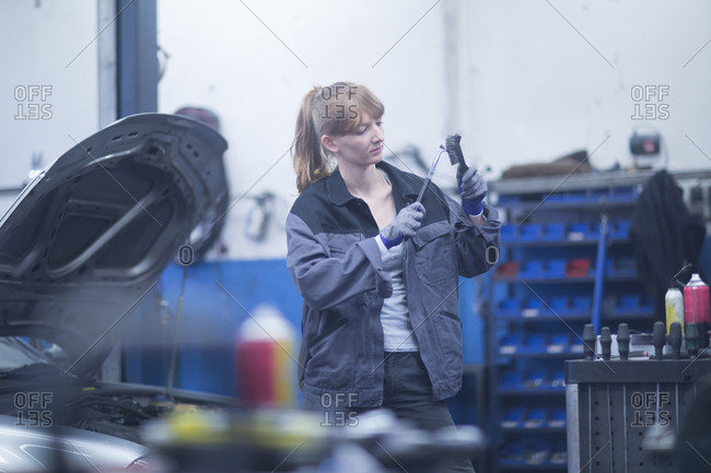 Female car mechanic working in repair garage