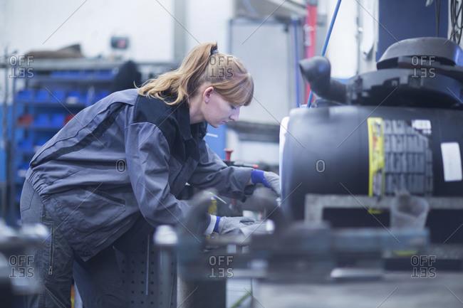 Female car mechanic working in repair garage