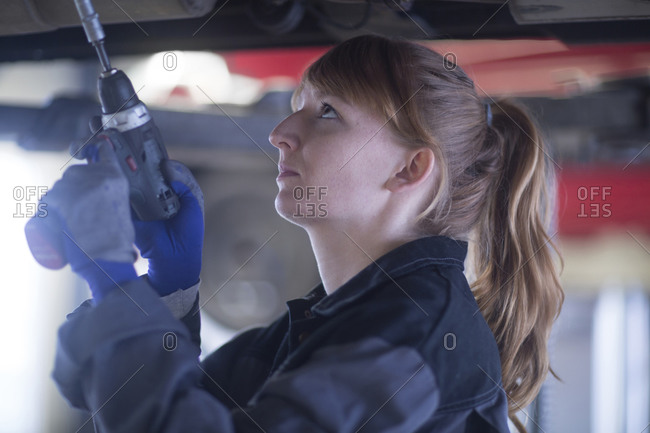 Female car mechanic fixing car standing under bottom in repair garage
