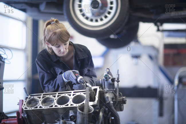 Female car mechanic fixing car in repair garage