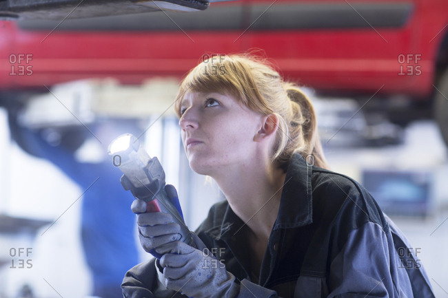 Female car mechanic with lamp looking to bottom of a car in repair garage