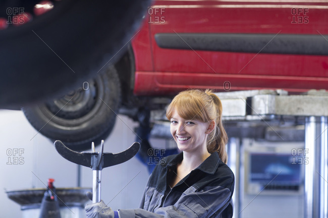 Smiling female car mechanic in repair garage