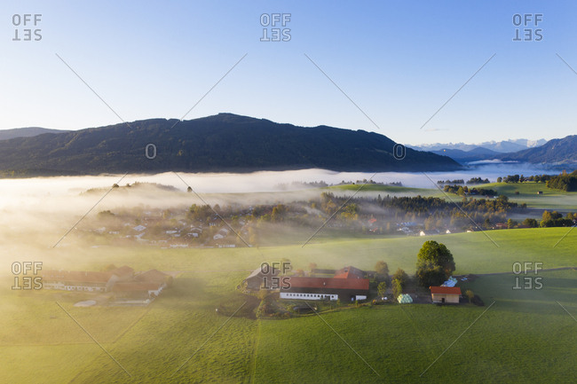 Germany- Upper Bavaria- Greiling- Aerial view of village and fields in fog at sunrise