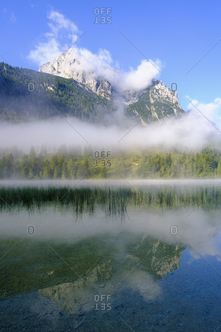 Germany- Bavaria- Mittenwald- Thick fog floating over Ferchensee lake with Wettersteinspitzen mountain in background