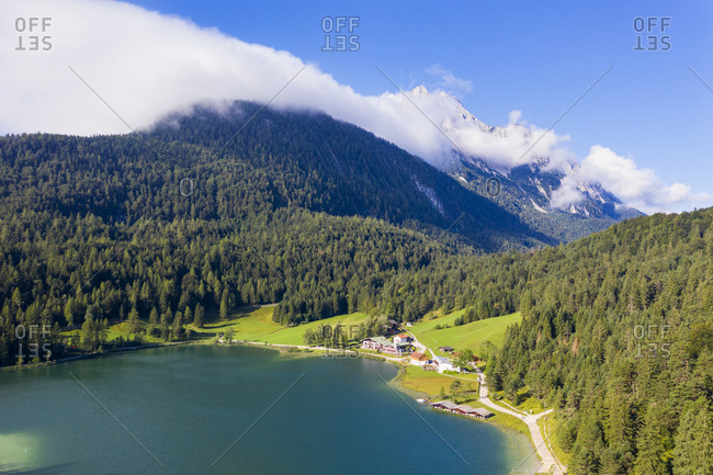 Germany- Bavaria- Mittenwald- Aerial view of Lautersee- forested Wetterstein Mountains and lakeshore village