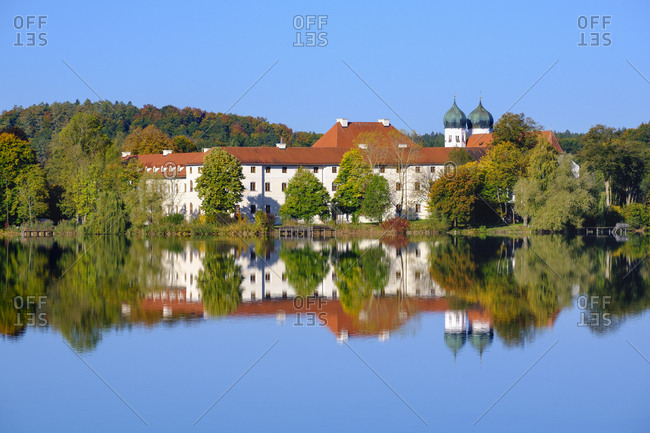 Germany- Bavaria- Seeon-Seebruck- Seeon Abbey reflecting in shiny Klostersee lake