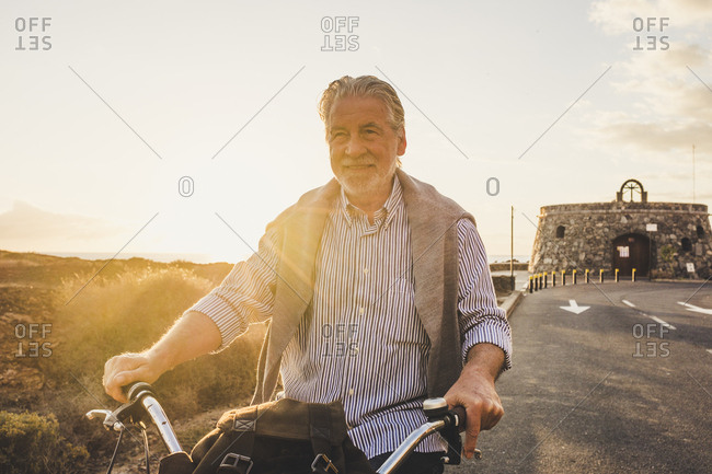 Senior man on bicycle at sunset- Tenerife