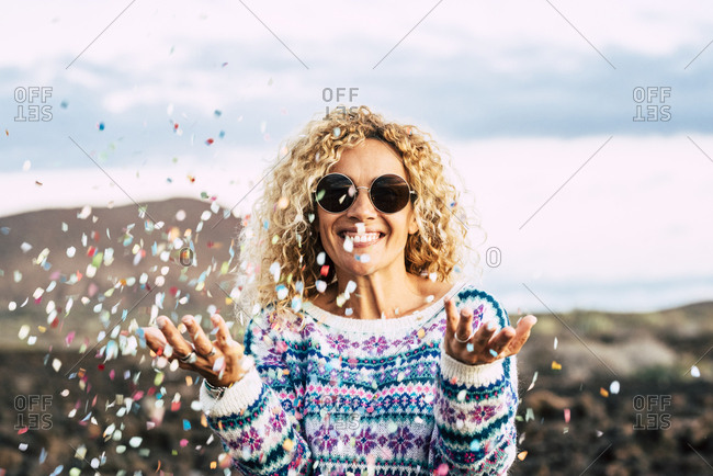 Portrait of happy blond woman celebrating with confetti- Tenerife- Spain