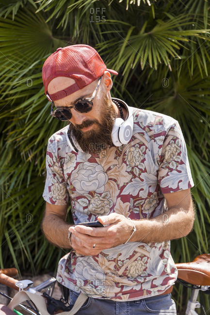Mature man with red basecap- sunglasses and white headphones using smartphone