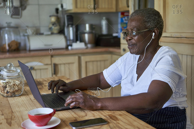 Senior woman sitting at kitchen table using laptop