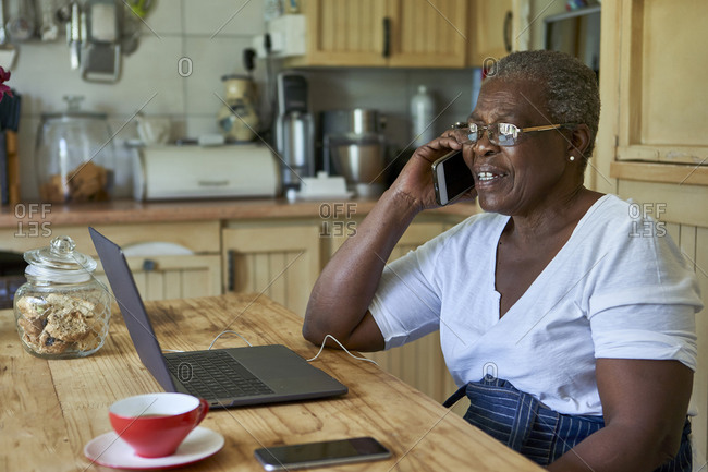 Senior woman sitting at kitchen table using laptop and smartphone