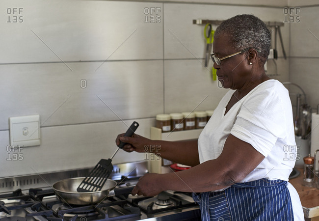 Senior woman cooking at gas stove in kitchen