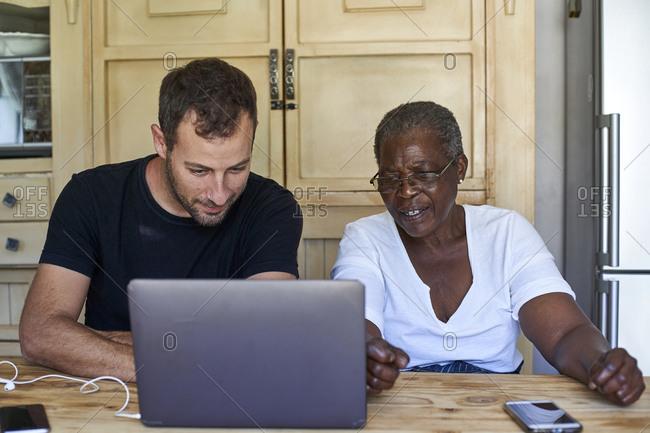 Senior woman and man sitting at kitchen table sharing laptop