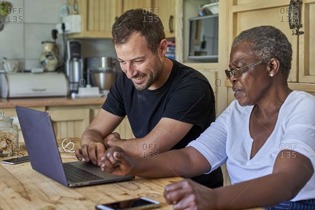 Senior woman and smiling man sitting at kitchen table sharing laptop