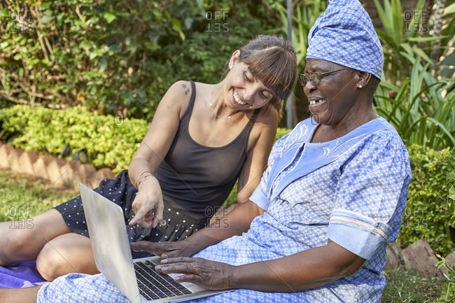 Happy senior woman sitting on lawn sharing laptop with a woman