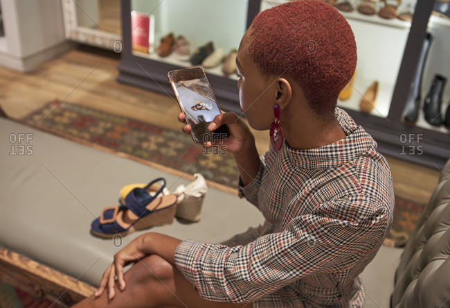 Young woman with colorful haircut taking a picture with her phone of a pair of shoes to buy at a clothes shop