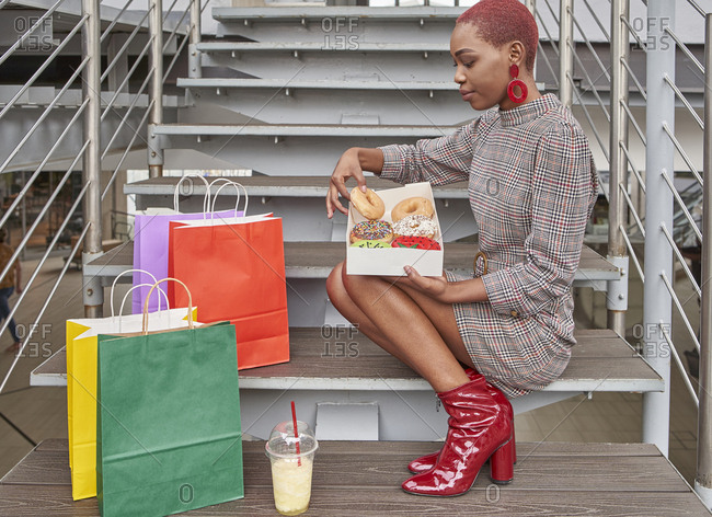 Young woman sitting on stairs surrounded by colorful shopping bags and eating a doughnut from the box