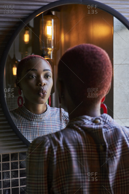 Young woman with short haircut looking to her reflection and sending a kiss in a round mirror