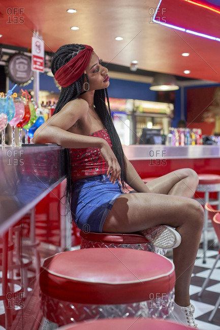 Young woman with braided hairstyle sitting on a bar on red stool