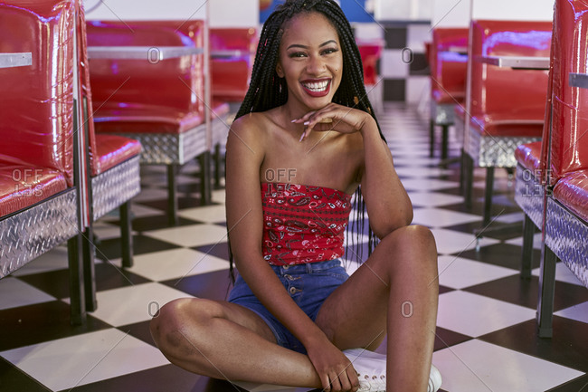 Smiling young woman with braided hairstyle sitting on the black and white floor of an American diner restaurant