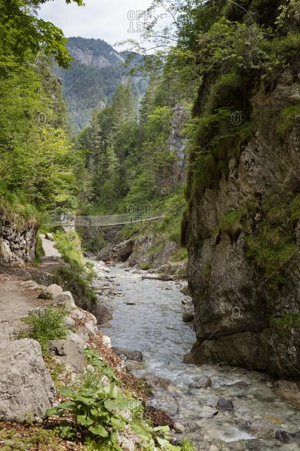 Austria- Tyrol- Erpfendorf- Stream flowing under suspension bridge in Griesbach Gorge