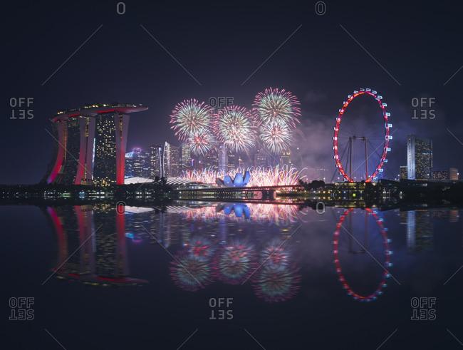 July 27, 2019: Singapore- Night firework display between Marina Bay Sands hotel and illuminated Ferris wheel