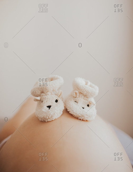 Fleece baby slippers on a pregnant woman's stomach